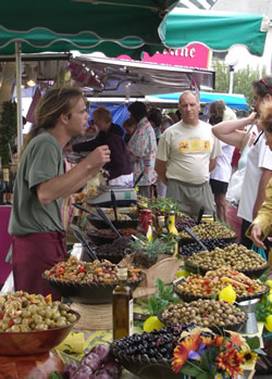 French market stall selling olives, garlic and marinated peppers