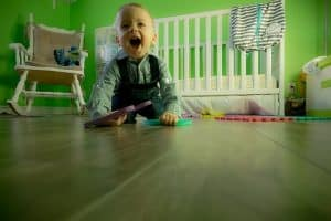 laughing toddler on wooden floor- white cot-white chair-some toys