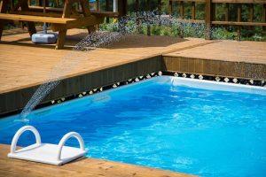 outdoor swimming pool-white steps-blue water-brown floor