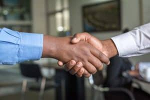 2 people in long sleeves shaking hands