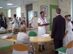 Maire wearing tri-coloured scarf celebrating marriage in France-bride-groom-witness