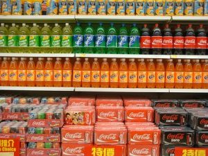 Several brands of cola bottles and cans on supermarket shelves