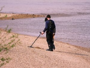 man on sandy beach with metal detector