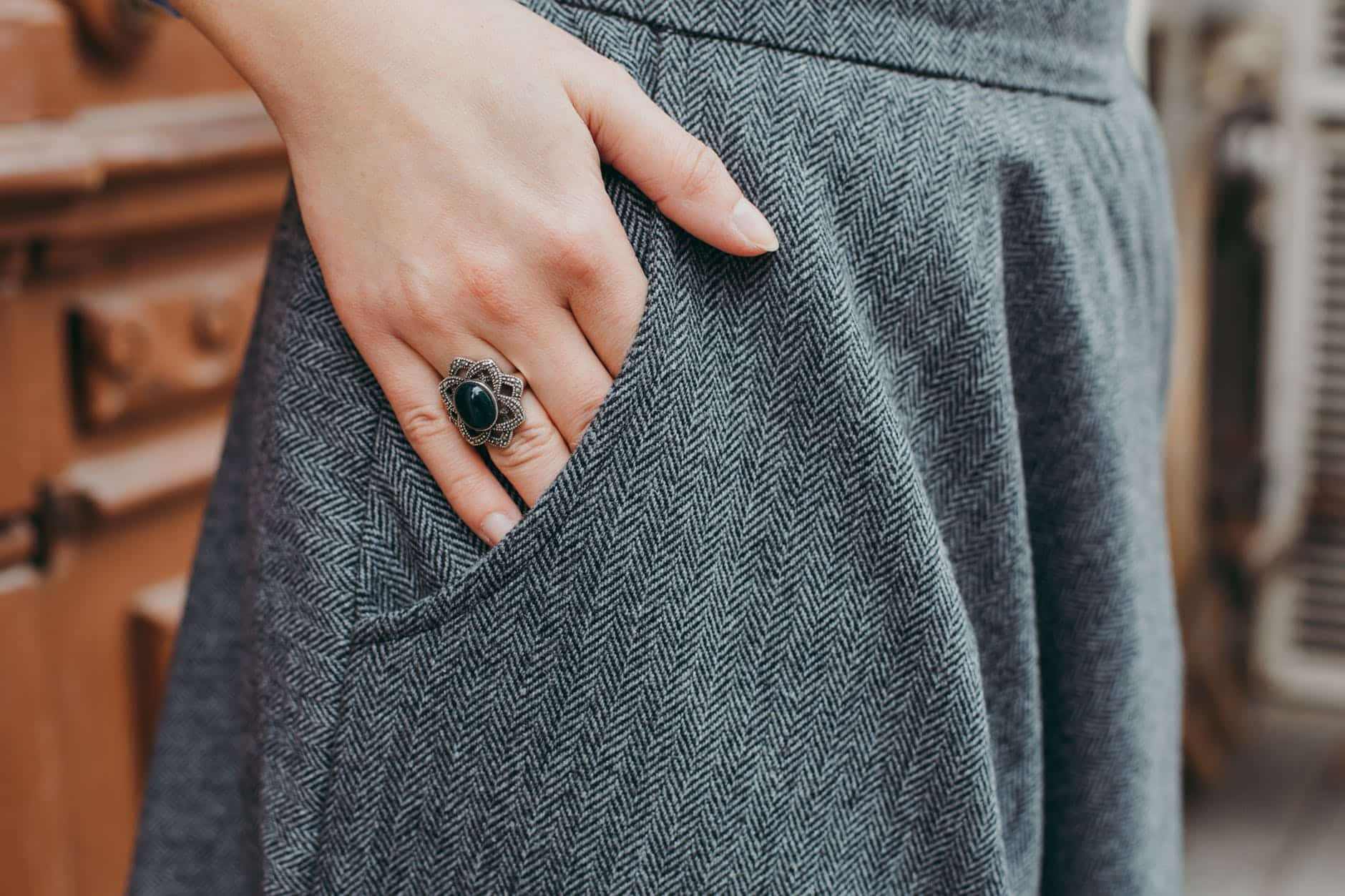 Woman's ringed hand in smart grey trouser pocket