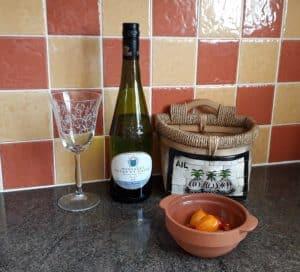 Bottle of Muscadet-wine glass-wicker garlic basket-cherry tomatoes in terracotta pot-terracotta tiles