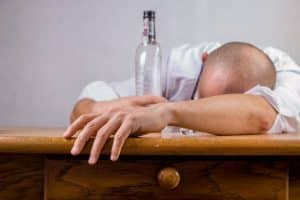 Drunk bald man wearing white shirt slouched on wooden table-empty bottle